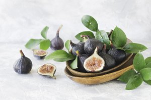 dark blue Fresh figs in a wooden bowl on a white marble table, selective focus