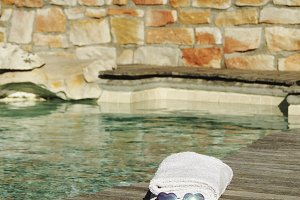 white towel and sunglasses the form of heart on the edge of a blue swimming pool, selective focus