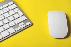 Keyboard of a computer and mouse on yellow background. Technology.