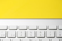 Keyboard of a computer on yellow background. Technology.