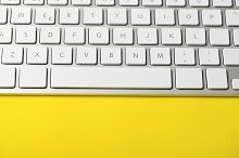 White keyboard of a computer on yellow background. Technology. Vertical shoot.