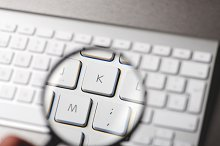 Magnifying glass over the letters of a keyboard over gray background. Technology.