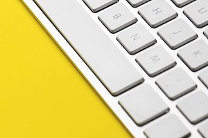 Keyboard of a computer on a yellow background. Vertical shoot.