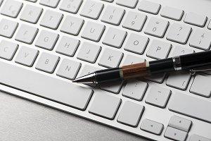 Ballpoint pen on a computer keyboard. Technology. Horizontal shoot.