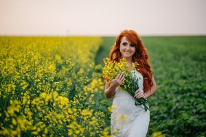 Young red-haired woman in a rapeseed field