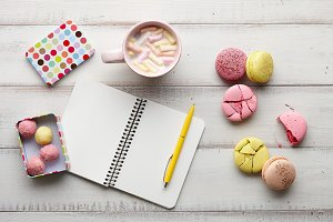 Hot chocolate, sweets and copybook on wooden table