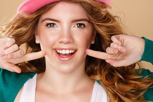 Girl with curly hair in a pink hat