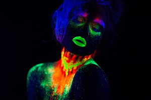 Beautiful extraterrestrial model woman with blue hair and green lips in neon light. It is portrait of beautiful model with fluorescent make-up, Art design of female posing in UV with colorful make up. Isolated on black background