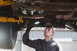 Car service - a mechanic checks the suspension of SUV
