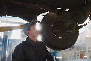 Garage automobile service - a mechanic checks the suspension, backlight