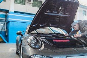 Mechanic in car garage checking hood of the luxury sportcar