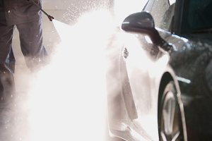 Mechanic in car service is washing sport car in the suds by water hoses, backlight
