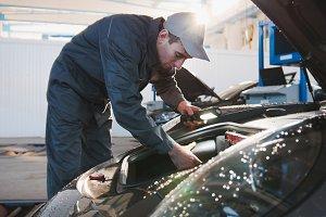 Mechanic male in automobile garage checking hood of luxury sportcar