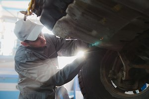Garage automobile service - a mechanic working the wheel, backlight