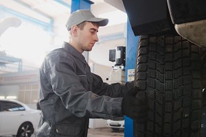 Garage automobile service - a mechanic working the wheel, close up