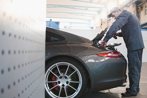 Mechanic in automobile garage checking hood for the luxury car