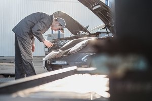 Mechanic in automobile garage checking hood for the luxury sport car