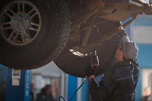 Mechanic is checking the wheel in garage automobile service
