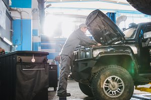Mechanic male in automobile garage checking hood of the car for luxury SUV, wide angle