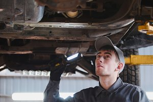 Mechanic with thr lamp is checking the bottom of car in garage automobile service, close up