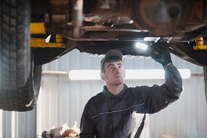 Mechanic with thr lamp is checking the bottom of car in garage automobile service, wide angle