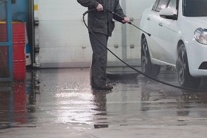 Worker in auto service is washing a car in the suds by water hoses