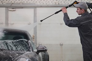 Worker in garage automobile service is washing a car in the suds by water hoses