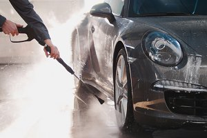 Worker in garage automobile service is washing a car in the suds by water hoses, close up