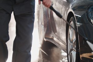 Worker in garage automobile service is washing a car in the suds by water hoses, detail close up