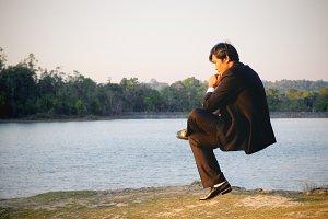 Businessman thinking at the lake