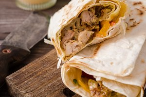 Shawarma chicken roll in a pita with fresh vegetables and cream sauce on wooden background. Selective focus