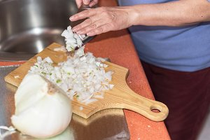 senior woman hand cutting onion.