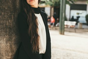 Businesswoman leans on tree