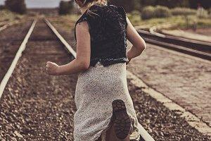 Girl running down traintracks