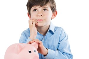 Boy with piggy bank thinking