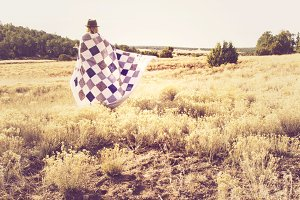 Woman and quilt on prairie