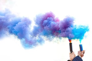 Hands holding colorful smoke bombs