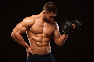 Handsome power athletic man with dumbbell confidently looking forward. Strong bodybuilder with six pack, perfect abs, shoulders, biceps, triceps and chest isolated on black background with copyspace