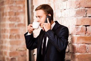 Young handsome businessman in black suit is drinking coffee and calling by the phone near brick wall