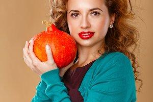 Girl holding a pumpkin.