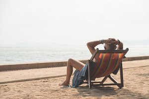 Senior man sunbathing on beach chair