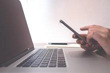 Female using smart phone on laptop