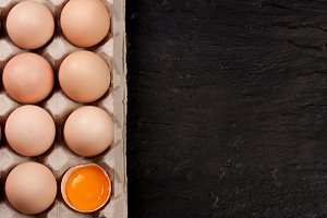 eggs in a tray on a dark background with copy space for your text. Top view