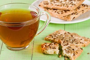crispy bread with seeds of sunflower, flax and sesame seeds with a cup of tea on a green wooden background