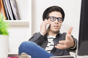 young modern man talking on cellphone in front of the computer in the office or at home