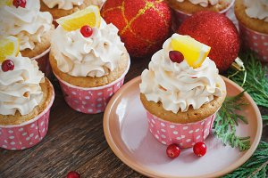 Christmas cupcakes with whipped cream topping and cranberries,orange. festive food dessert.