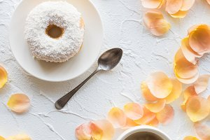 Cup of coffe and a donut on white textured background