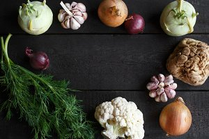 Spring vegetables on a dark background: cauliflower, onion, garlic, kohlrabi, celery root, dill