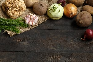 Spring vegetables on a dark background: onion, garlic, kohlrabi, celery root, dill, beets, potatoes