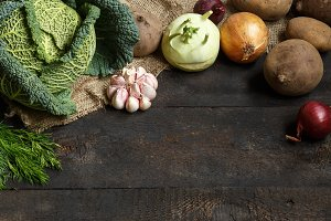 Spring vegetables on a dark background: Savoy cabbage, cauliflower, onion, garlic, kohlrabi, celery root, dill